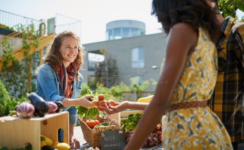 Vänlig kvinna som ansar en organisk grönsakstall på en bondes marknad och säljer nya grönsaker från taket arkivbilder