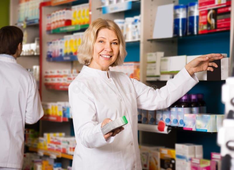 Vänlig kvinnlig apotekare på arbete royaltyfria bilder