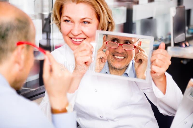 Vänlig kvinnlig optiker som konsulterar den mogna manliga kunden royaltyfri foto
