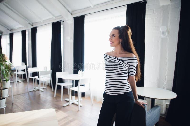 Vänlig le kvinna för stående som drömmer eller tänker i en studio Härlig brunn-ansad medelålders kvinna hemma royaltyfria bilder