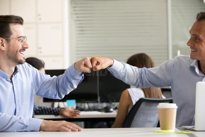 Vänlig le manlig kolleganäve som knuffar till på arbetsplatsslutet upp royaltyfria foton