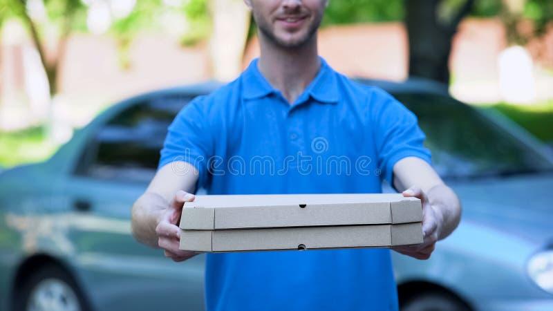 Vänlig leveransman som direktanslutet ger pizzaasken, matbeställning, restaurangservice royaltyfri foto