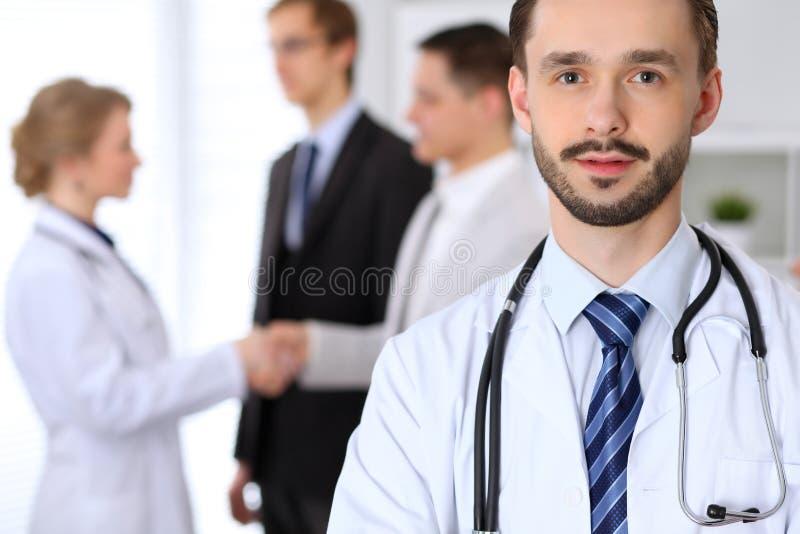 Vänlig manlig doktor på den bakgrundsdoktorn och patienten som skakar händer Medicinskt förtroende och etikbegrepp royaltyfria bilder
