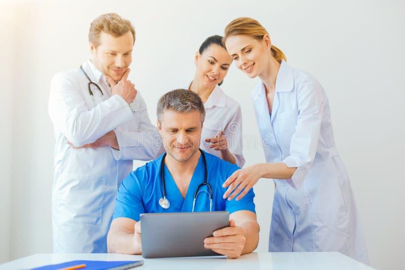 Vänlig medicinsk professionell som ser bärbara datorn och att le royaltyfri fotografi
