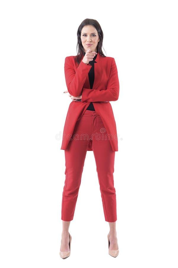 Vänlig säker lycklig affärskvinna i röd dräkt som pekar fingret på skärmen som väljer dig arkivfoton