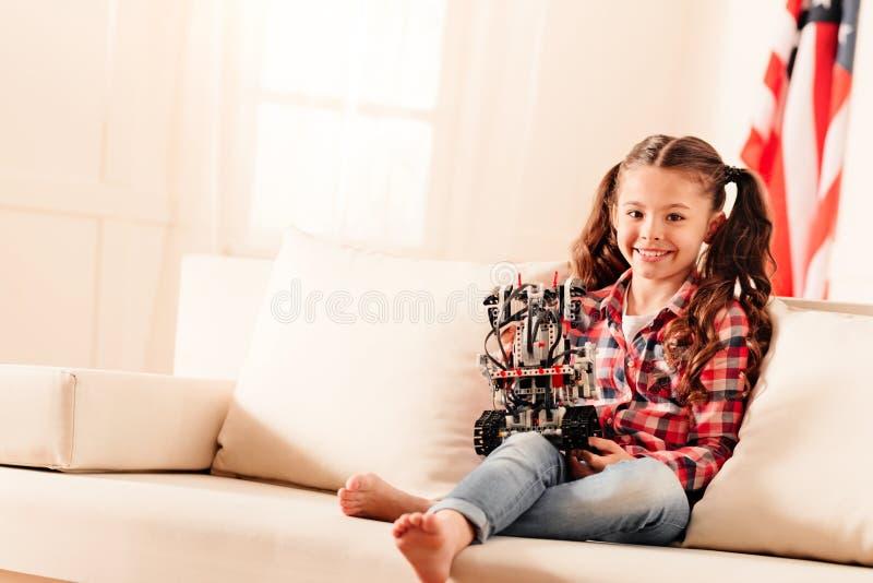 Vänlig seende flicka med robotleksaken som ler in i kamera arkivfoto