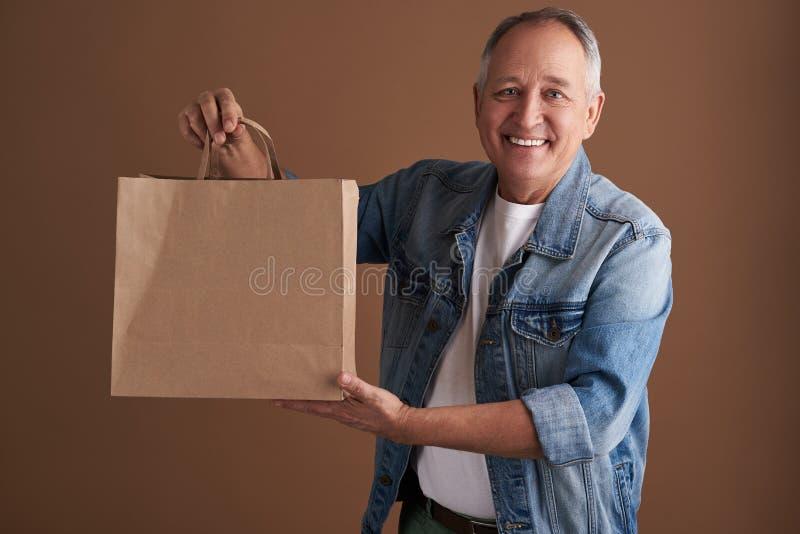 Vänlig seende man som ler och visar papperspåsen royaltyfri foto
