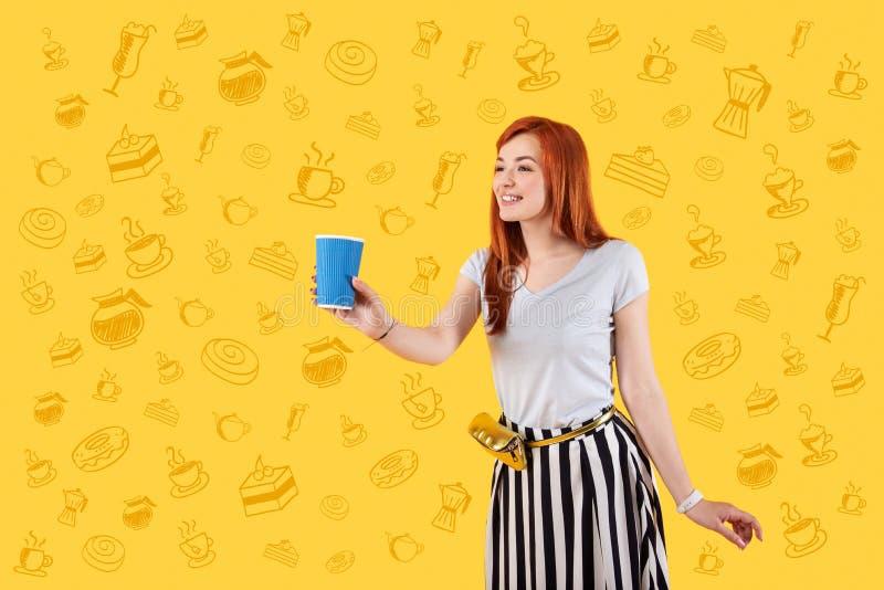Vänlig servitris som ler och erbjuder ett exponeringsglas av kaffe royaltyfri foto