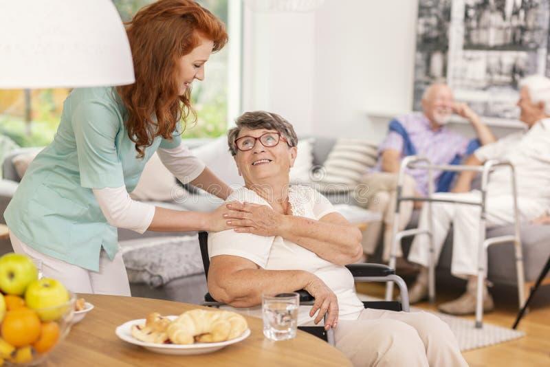 Vänlig sjuksköterska som stöttar le den höga kvinnan i sjukvårdhus arkivbild