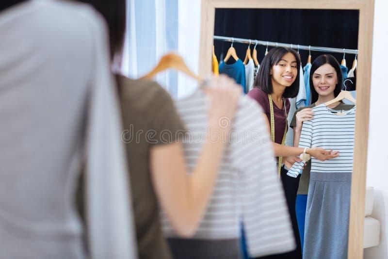Vänlig skräddare som förklarar idén av band på en ny klänning royaltyfria bilder