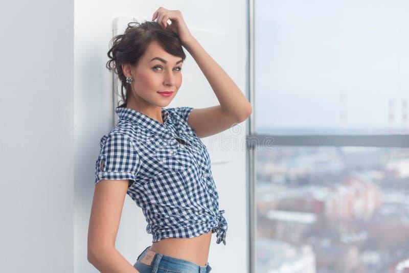 Vänlig trevlig avkopplad flicka som poserar i den moderna ljusa studion som bär den moderiktiga tillfälliga dräkten, rörande hår  royaltyfria foton