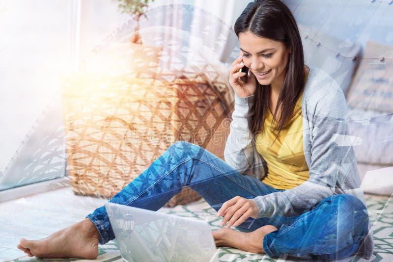 Vänlig ung kvinna som talar på telefonen, medan sitta hemma arkivbilder