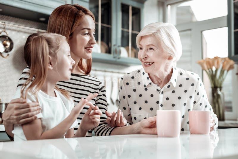 Vänliga kvinnor av en familj som sitter på köksbordet och samtalet arkivfoton