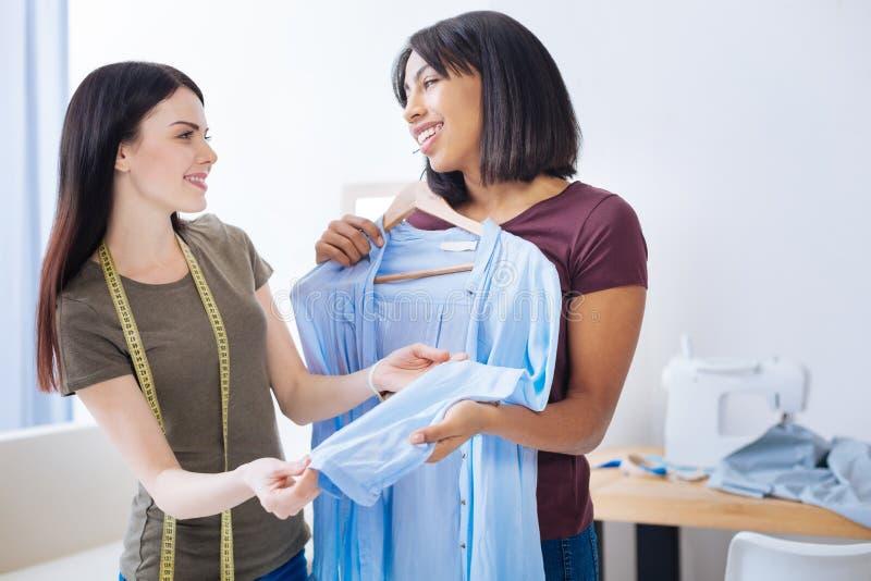 Vänliga kvinnor som ler, medan diskutera en härlig blus fotografering för bildbyråer