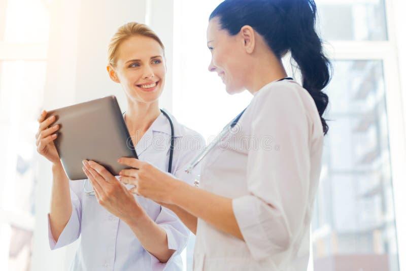 Vänliga läkare som ler, medan genom att använda minnestavladatoren på arbete royaltyfri fotografi