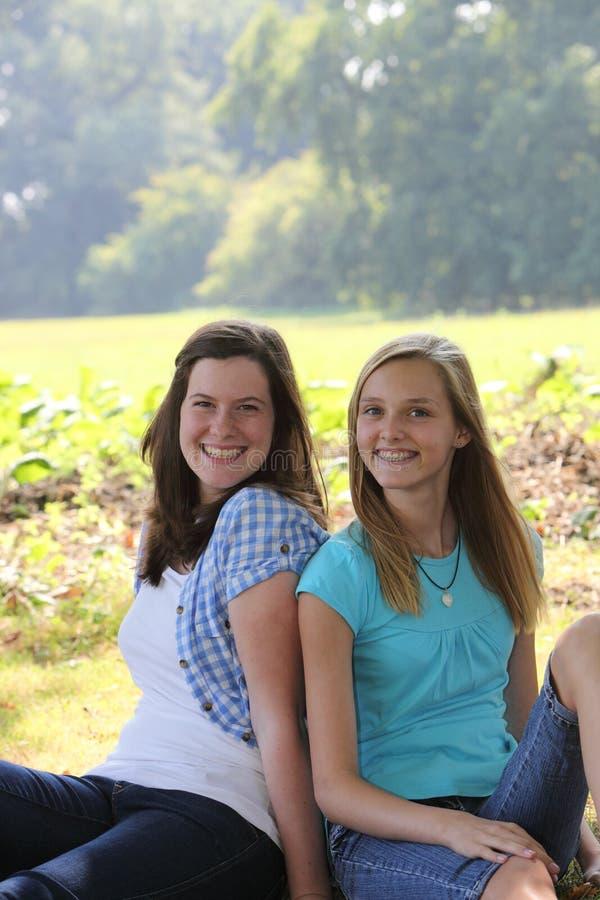 Vänliga lyckliga tonårs- flickor i parkera arkivbild