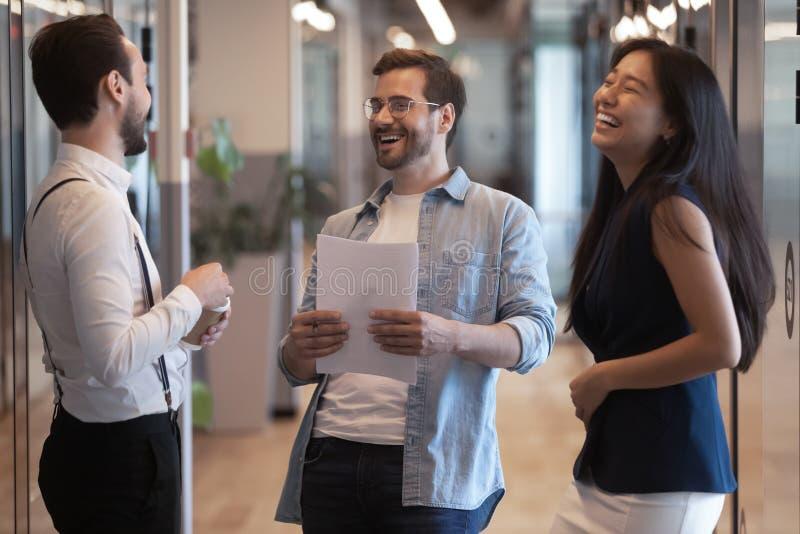 Vänliga lyckliga tre olika kollegor som talar att skratta på arbetsavbrottet fotografering för bildbyråer