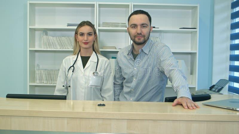 Vänliga man- och kvinnligsjuksköterskor bak mottagandeskrivbordet i sjukhus arkivfoton