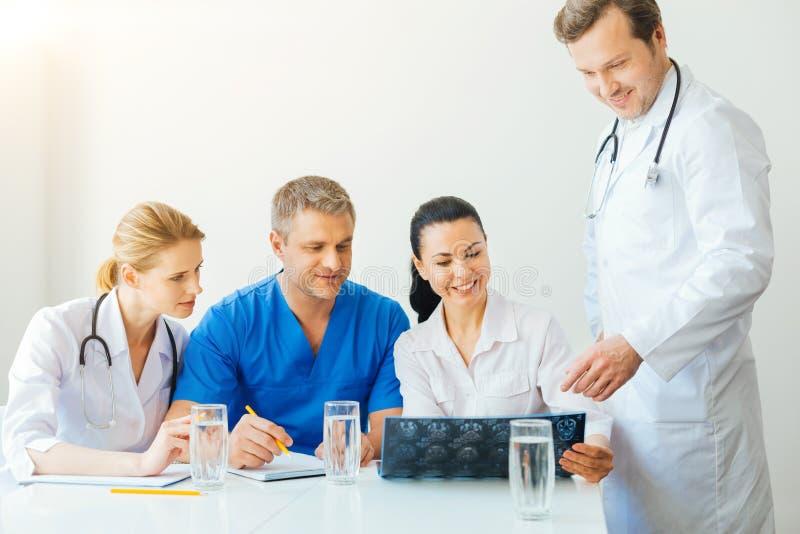 Vänliga medicinska coworkers som pratar över sjukdom av patienten arkivbild