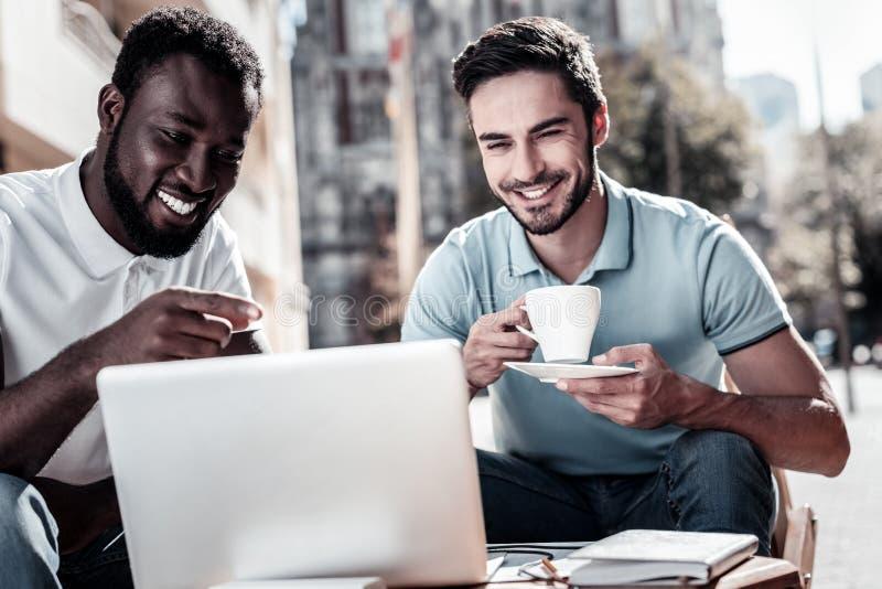 Vänliga millennial kollegor som diskuterar projekt i lokalt kafé arkivfoto
