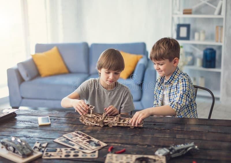 Vänliga pojkar som ler, medan arbeta på deras träkonstruktör royaltyfri fotografi