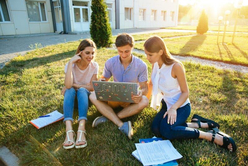 Vänliga studenttonåringar med bärbara datorn studerar utomhus tillsammans royaltyfri foto