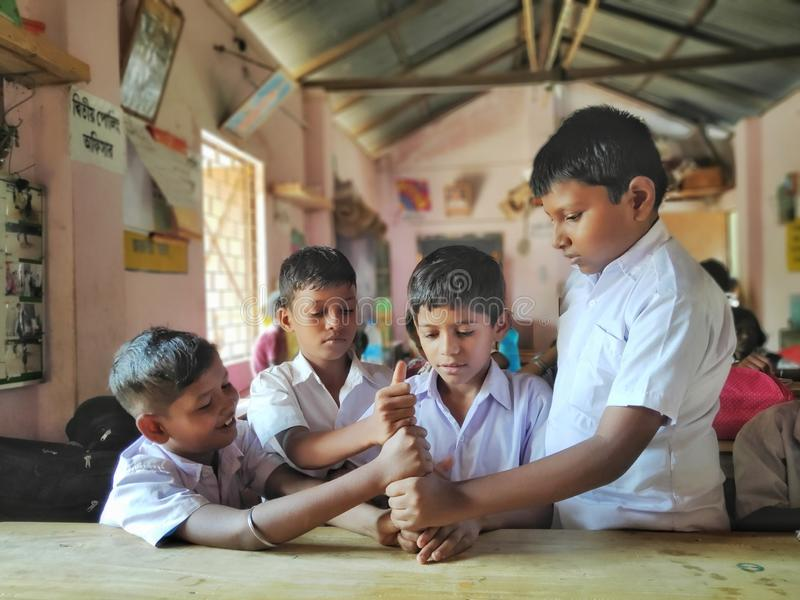 vänliga ungar i skolalikformign som spelar lekar med smily framsidor i en lokal bygrundskola för barn mellan 5 och 11 år arkivbild