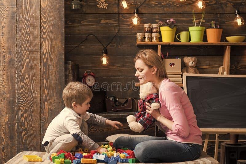 Vänlighet- och utbildningsbegrepp Modern undervisar sonen att vara snäll och vänlig Familjlek med nallebjörnen hemma Mamma och arkivbilder