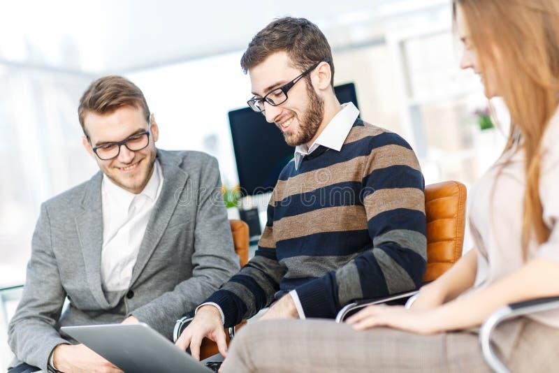 vänligt affärslag som arbetar på bärbara datorn och diskuterar affärsfrågor arkivbilder