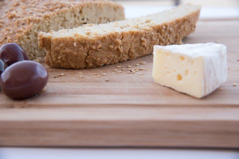 Vänligt bröd för Keto med ost och oliv på en skärbräda arkivbilder