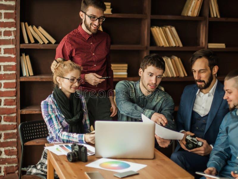 Vänligt lag av copywriter i arbetsplatsen i modernt kontor royaltyfri foto