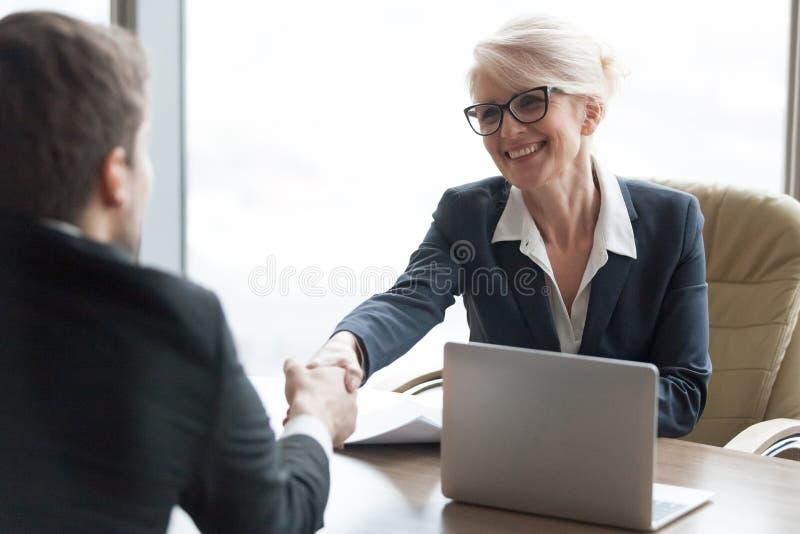 Vänligt sökande för timme-chefhandshaking som hyr kandidaten på jobbintervjun arkivfoto