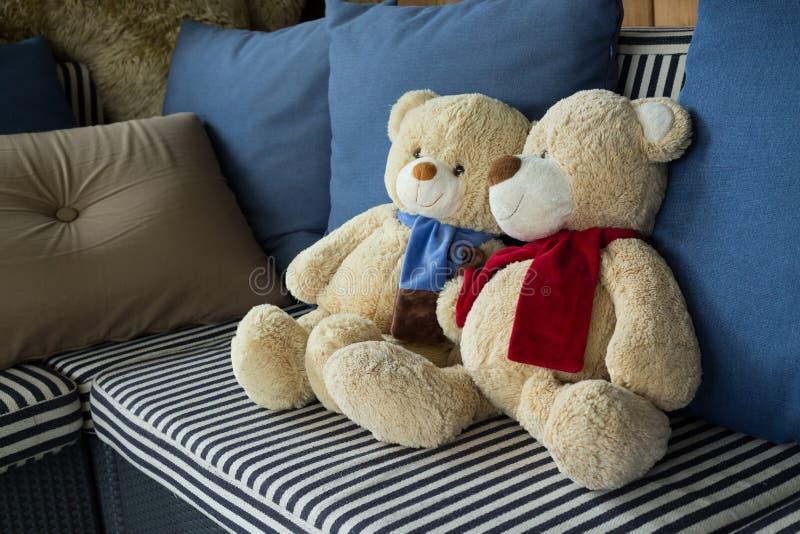 Vännen för pardockabjörnen dekorerade på soffamöblemanginre arkivbild