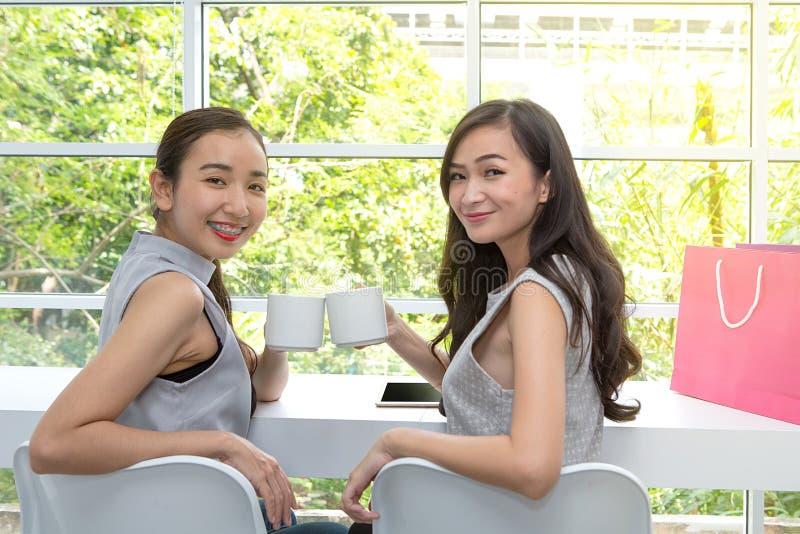 Vänner är lyckliga i coffee shop Två tal vänner eller systrar arkivfoto