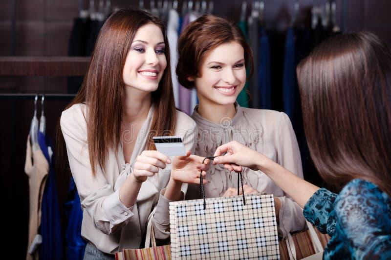 Vänner betalar med kreditkorten arkivfoto