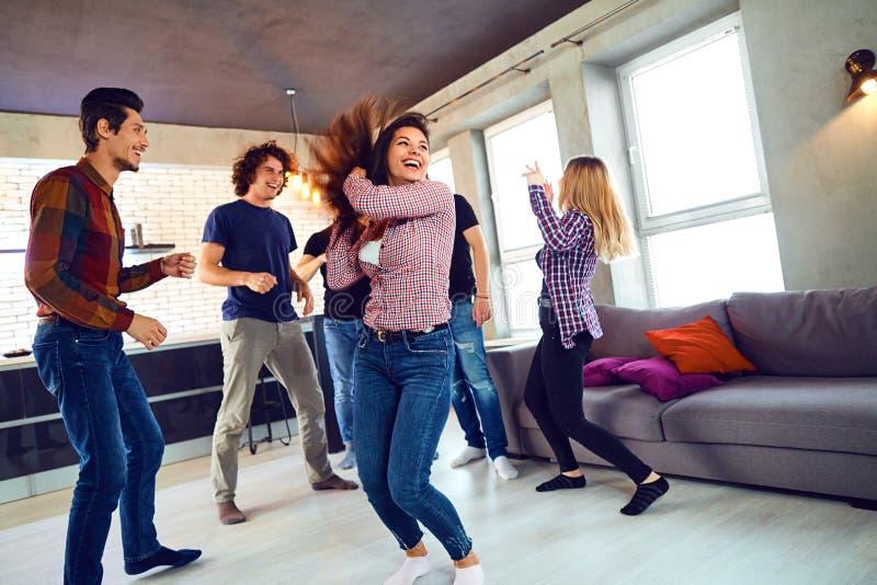 Vänner dansar på ett parti för student` s i lägenheten royaltyfri bild