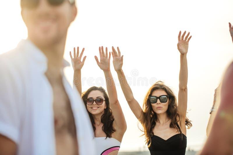 Vänner dansar på stranden under solnedgångsolljus och att ha gyckel som är lycklig, tycker om arkivbilder