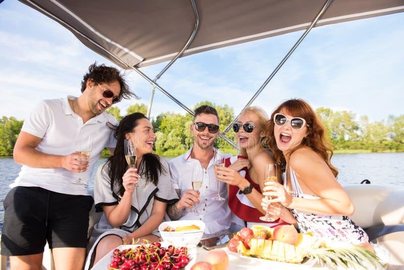 Vänner dricker champagne på yachten arkivfoto