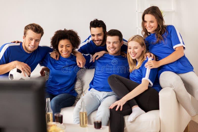 Vänner eller fotbollsfan som hemma håller ögonen på fotboll royaltyfri foto