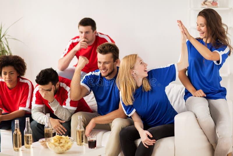 Vänner eller fotbollsfan som hemma håller ögonen på fotboll royaltyfria foton