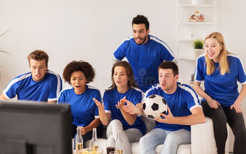 Vänner eller fotbollsfan som hemma håller ögonen på fotboll royaltyfria bilder