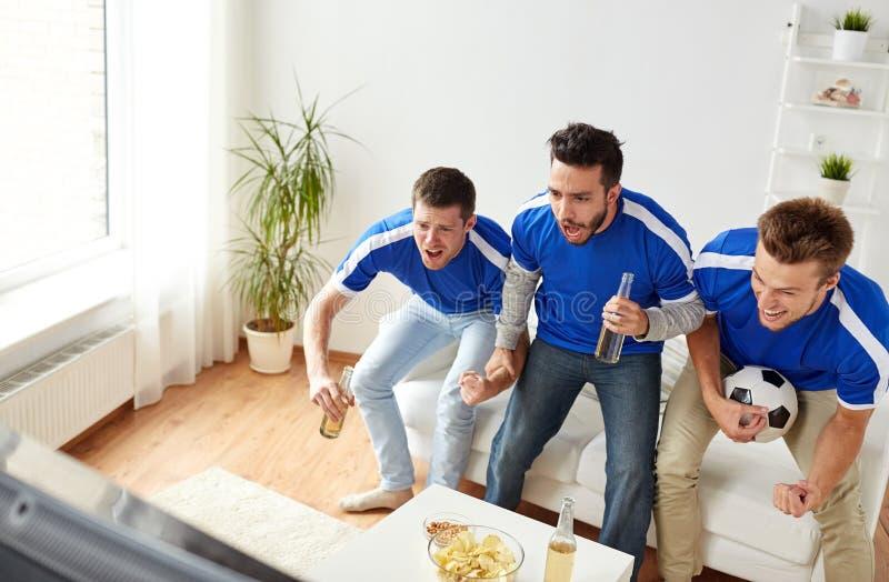 Vänner eller fotbollsfan som hemma håller ögonen på fotboll arkivbilder