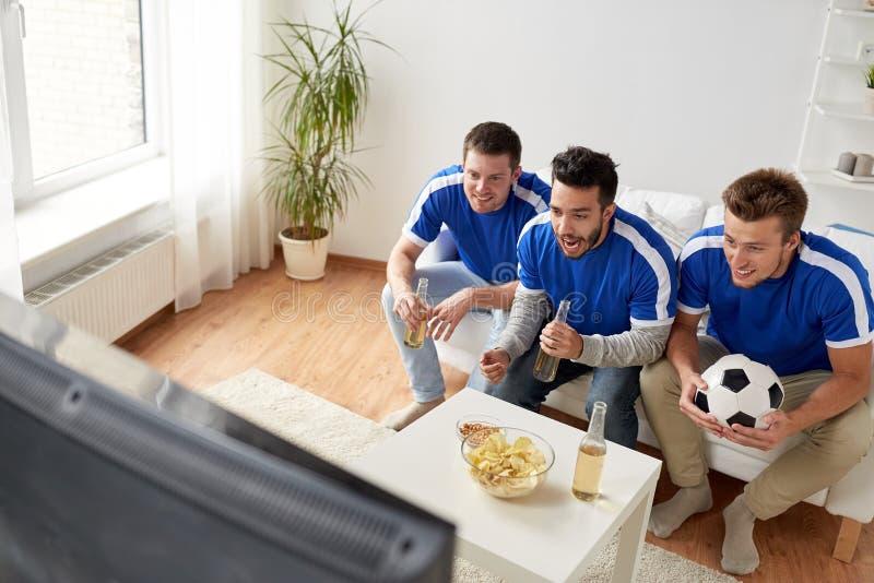 Vänner eller fotbollsfan som hemma håller ögonen på fotboll arkivfoto