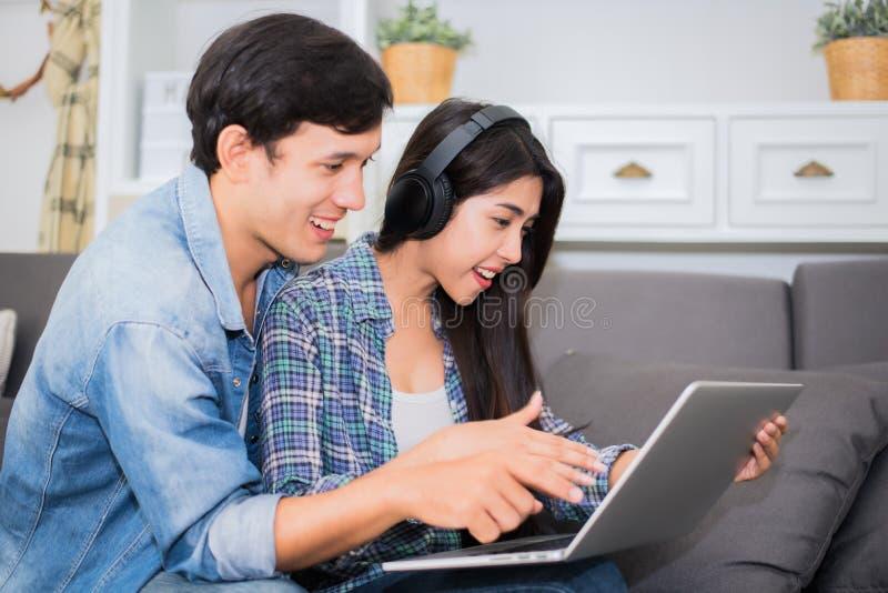 Vänner eller par genom att använda bärbara datorn och lyssnande musik med headphonen i hus Bröllopsresa- och underhållningbegrepp arkivfoto
