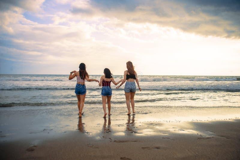 Vänner eller systrar för unga kvinnor som tillsammans spelar i stranden på solnedgångljus som har gyckel som tycker om sommarferi royaltyfria foton