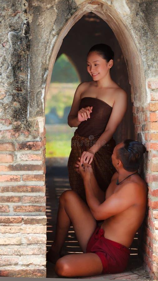 Vänner för asiat som två flörtar i hemlighet inom templet Thailändska man- och kvinnligmodeller med traditionella och kulturella  arkivbild
