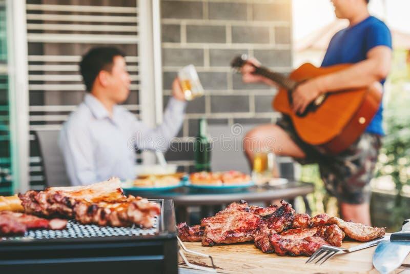 Vänner för eftermiddagpartigrupp som tycker om dricka öl med den lyckliga spela gitarren för grillfest- och stekgriskött som tyck arkivbilder