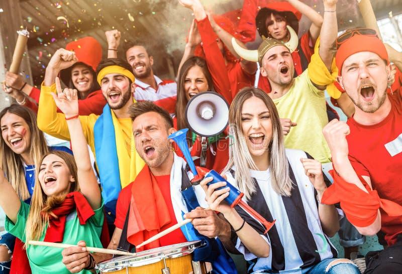 Vänner för fotbollsupporterfans som hurrar och håller ögonen på fotbollkoppen royaltyfri bild