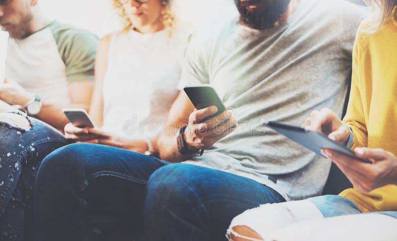 Vänner för Hipsters för Closeupgrupp som vuxna sitter Sofa Using Modern Gadgets Begrepp för teamwork för kamratskap för affärssta fotografering för bildbyråer