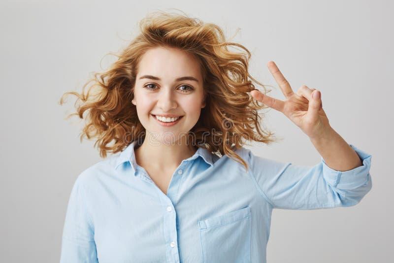 Vänner för pojkvänner Inomhus skott av den positiva snygga kvinnan med lockigt hår och att visa seger eller fredgest arkivbild